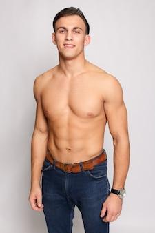 Фитнес, спорт, люди, концепция здорового образа жизни - портрет молодого мускулистого мужчины с голым торсом, стоящего с руками, скрещенными на белой стене. очень мускулистая мужская модель без рубашки в джинсах