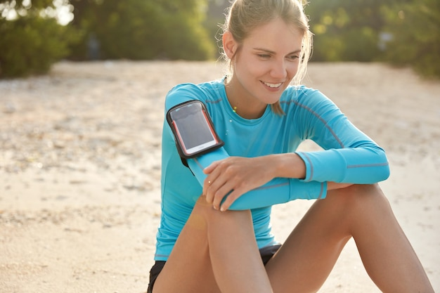 Fitness, sport, technology, people and exercising concept. pleased satisfied female wears pulsometer while trains outdoor over beach sunset background, works on her body, keeps fit and healthy