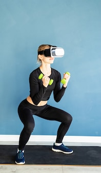 Fitness, sport and technology. young athletic woman wearing virtual reality glasses squatting with dumbbells at blue background