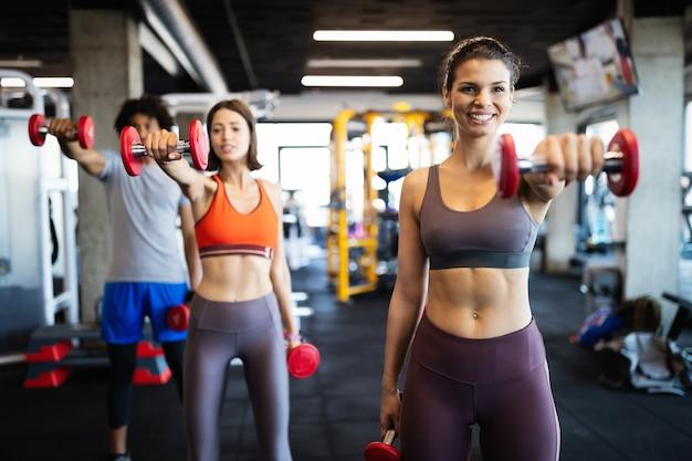 피트 니스, 스포츠, 훈련 및 라이프 스타일 개념입니다. 체육관에서 운동하는 맞는 사람들의 그룹