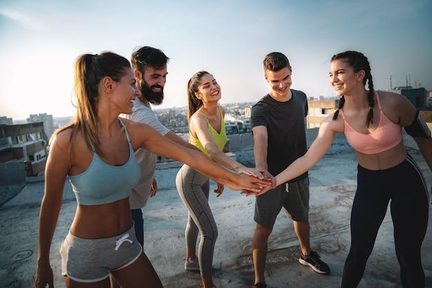 피트 니스, 스포츠, 훈련 및 라이프 스타일 개념입니다. 야외에서 운동하는 웃는 행복한 사람들의 그룹