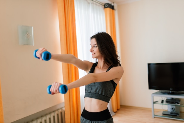 フィットネス、スポーツ、トレーニング、ライフスタイルのコンセプト-彼女の家での笑顔の女性のトレーニング