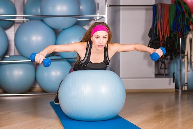 Концепция фитнеса, спорта, тренировок и образа жизни - улыбающаяся женщина с гантелями и мячом для упражнений в