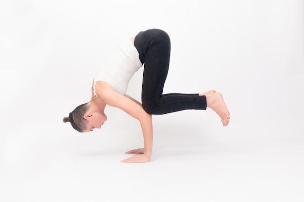 フィットネス、スポーツ、トレーニング、ライフスタイルのコンセプト-ヨガの練習をしている若い女性。ヨガの練習をしている白いスポーツウェアの若い美しい少女の肖像画。ストレッチ運動をしている女性