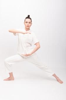 피트니스, 스포츠, 훈련 및 라이프스타일 개념 - 요가 운동을 하는 젊은 여성. 체육관에서 태극권을 수련하는 젊은 여성. 중국 관리 기술 제나라의 에너지.