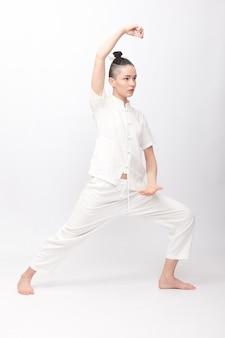 フィットネス、スポーツ、トレーニング、ライフスタイルのコンセプト-ヨガの練習をしている若い女性。ジムで太極拳を練習している若い女性。中国の管理スキルチーのエネルギー。
