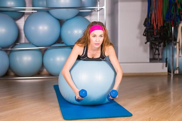 Фитнес, спорт, тренировки, технологии будущего и концепция образа жизни - улыбающаяся женщина с гантелями и мячом для упражнений в тренажерном зале и проекции