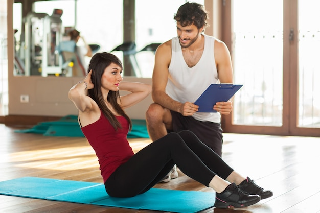 Fitness, sport, training, gym and lifestyle concept - woman with personal trainer