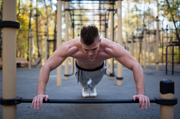 Fitness, sport, training and lifestyle concept - young adult fit man doing push-ups outdoors, healthy lifestyle