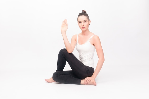 Fitness, sport, training and lifestyle concept - young woman doing yoga exercise. portrait of young beautiful girl in white sportswear doing yoga practice.woman doing stretching exercise