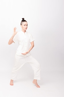 Fitness, sport, training and lifestyle concept - young woman doing yoga exercise. young woman praticing tai chi chuan in the gym. chinese management skill qi's energy.