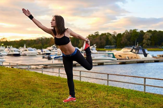 屋外のクロストレーニングトレーニング中に脚でストレッチをしているフィットネススポーツの女性。明るい太陽の下で黒いタンクトップとタイツの女性。