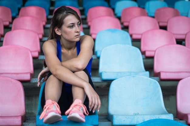 Fitness sport woman in fashion sportswear, sits looking at running sport woman, fitness exercise in the stadium. healthy lifestyle concept.