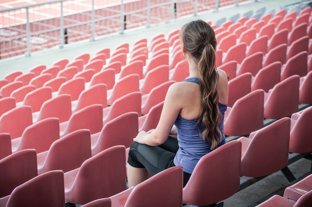 Fitness sport woman in fashion sportswear, sits looking at running sports woman, fitness exercise in the stadium. healthy lifestyle concept.