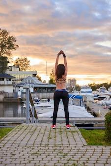 フィットネススポーツの女性は、集中的な夜のランニングの後に休息を取り、屋外でジョギングした後に休憩をとる若い魅力的な女の子、夕日を見ている黒いスポーツウェアの女性ジョガー、垂直写真。