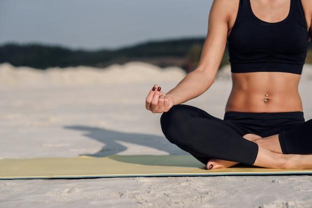 フィットネススポーツヨガと健康的なライフスタイルのコンセプト。砂の背景に座りやすい位置で瞑想している美しい少女の肖像画を閉じます。