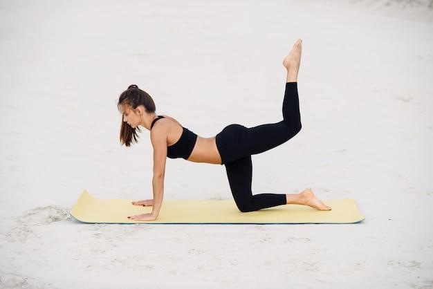 フィットネススポーツヨガと健康的なライフスタイルのコンセプト。ビーチでスポーティなヨガの女の子は、彼女の手にもたれてバックキックを練習します。