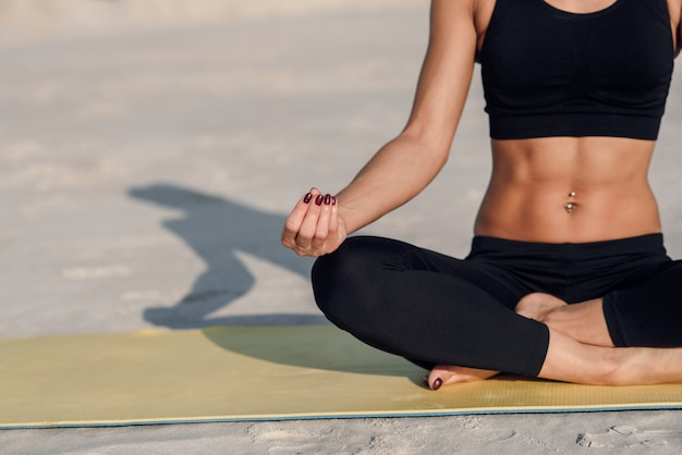Fitness sport yoga and healthy lifestyle concept. close up portrait of beautiful girl meditating in easy sitting position on the background of sand.