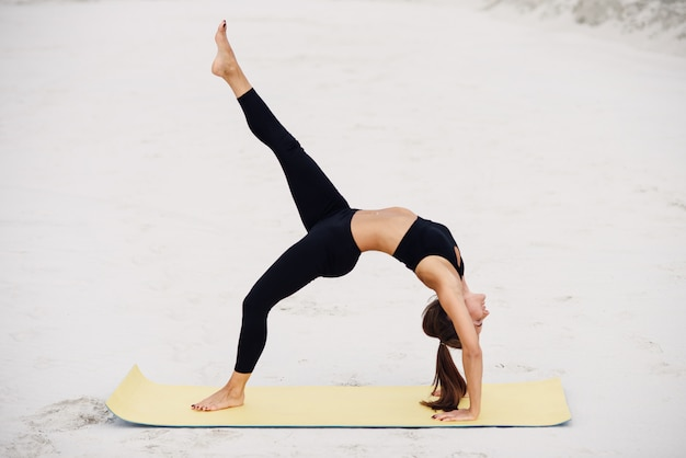 Fitness sport yoga and healthy lifestyle concept. sporty yoga girl on the beach practices backward kicks leaning on her hands.