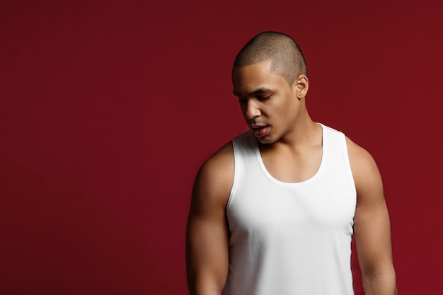 Fitness, sports, active and healthy lifestyle concept. stylish young mixed race athletic 20 year old man with muscular shoulders standing isolated at red copyspace studio wall, looking down