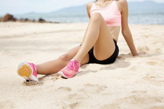 フィットネス、スポーツ、健康的なライフスタイルのコンセプト。ぼやけた海とビーチに座ってアクティブな運動後リラックスした女性ランナー