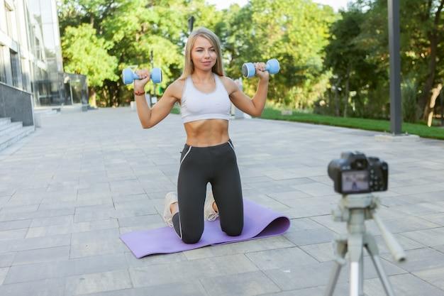 Концепция фитнеса, спорта и видеоблогов. женский спортивный блоггер с камерой на штативе записывает фитнес-тренировку на открытом воздухе с гантелями