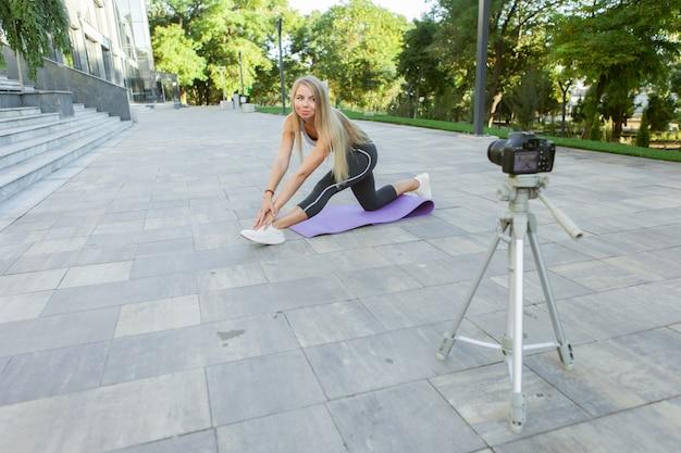 Концепция фитнеса, спорта и видеоблогов. женский спортивный блоггер с камерой на штативе, записывающей фитнес-тренировку на открытом воздухе