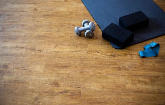 Комплект спортивного оборудования для фитнеса с ковриком для йоги и гантелями на полу тренажерного зала