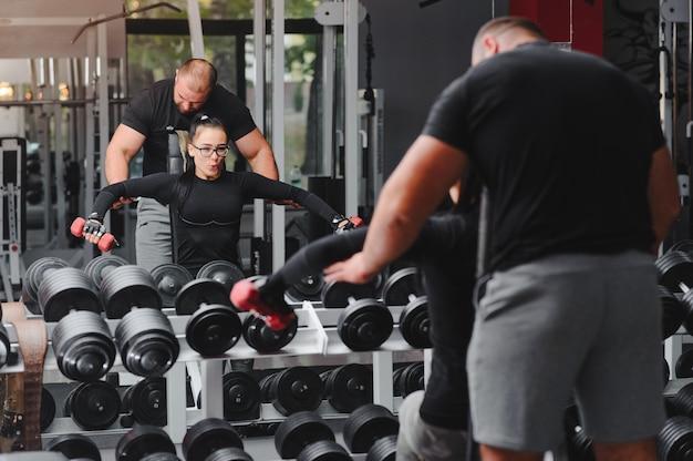 Фитнес, спорт, упражнения и тяжелая атлетика. концепция - молодая женщина и молодой человек с гантелями размахивая мускулами в тренажерном зале.