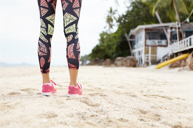 Fitness, sports and people. female jogger with muscular athletic legs in colorful leggings standing on sandy beach during her outdoors jogging exercises.