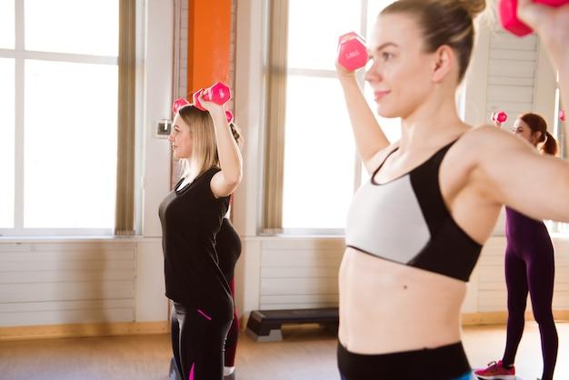 피트니스, 스포츠, 교육, 체육관 및 라이프 스타일 개념-체육관에서 스테퍼와 함께 일하는 여성 그룹.