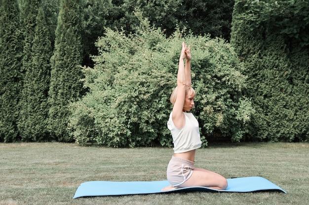 Фитнес, спорт, йога на свежем воздухе, в лесу. молодая женщина на природе занимается спортом. здоровый образ жизни.