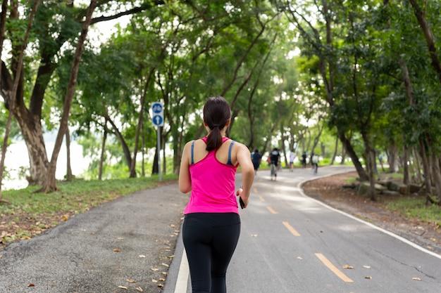 Fitness sportswoman exercise running on park trail in the morning.