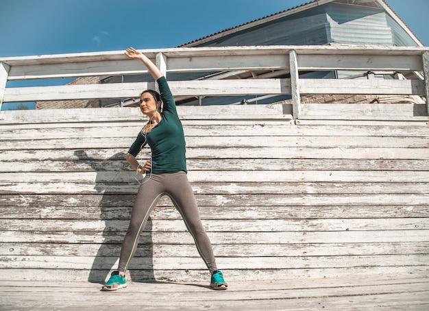 スポーティな服でフィットネススポーティな女の子は、木製の背景、明るい背景、スポーツの概念の演習を行っています