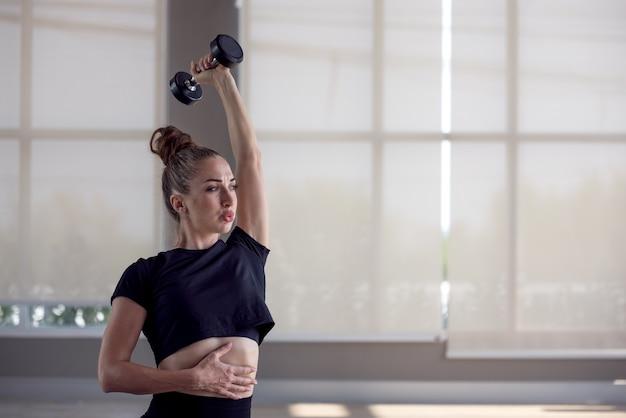 피트니스 스포티 한 여자는 아령, 힘 및 동기 부여와 함께 운동을합니다.