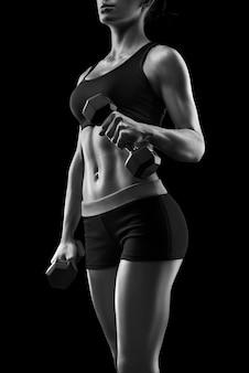 ダンベルで筋肉をポンピングするトレーニングのフィットネススポーティな女性。孤立した、黒い背景にポーズをとるダンベルを持つ若いスポーツセクシーなフィットネス女性の体。