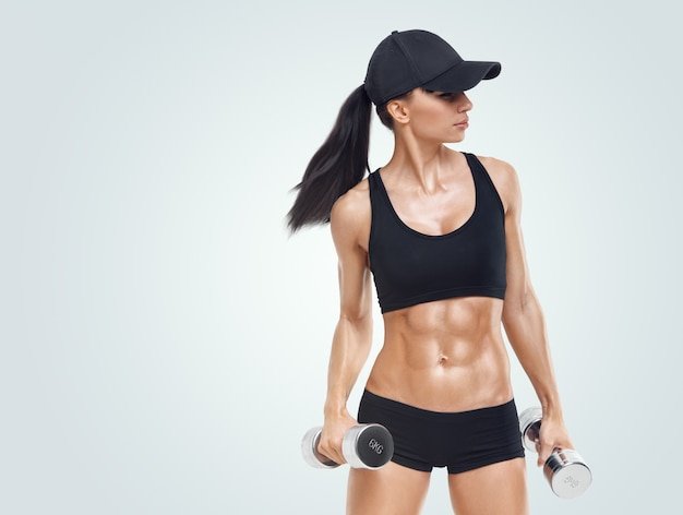 Fitness sporty woman in training pumping up muscles
