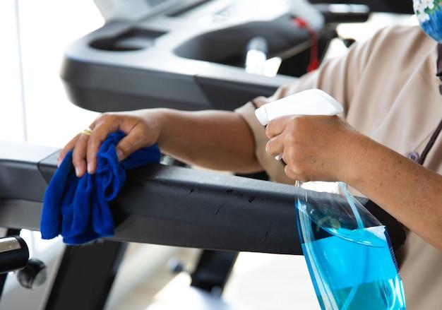 Персонал фитнеса чистит тренажеры спиртовым дезинфицирующим средством. горничная работает уборкой в тренажерном зале.