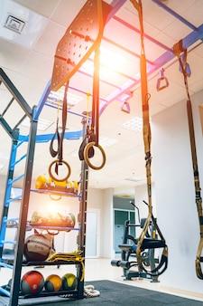 フィットネスストラップ:トラクションおよびサスペンショントレーニング機器のオンジムの背景。スポーツをするための近代的な設備。閉じる