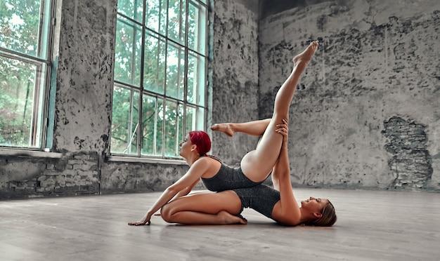 Фитнес, практика растяжки, группа двух привлекательных женщин, занимающихся йогой. концепция оздоровления. партнерская йога. баланс, концентрация, концепция равновесия.
