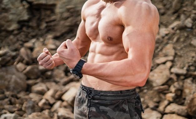 岩が多いバックグラウンドで握りこぶしでポーズフィットネスストロングマン。ボディービルダーコンセプトの背景-筋肉ボディービルダーは筋肉をポンピングします。半分裸の若い男性。裸の胴体。筋肉の手のクローズアップ。