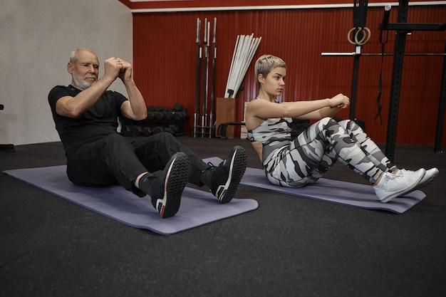 Concetto di fitness, lavoro di squadra, sport e formazione. due persone attive sportive senior maschio e giovane femmina bionda che si siede sulle stuoie e che esegue arricciature o scricchiolii durante un intenso allenamento crossfit in palestra