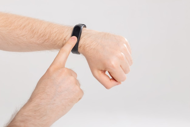 Fitness and technology concept - activity tracker on a male wrist on white wall with copy space.