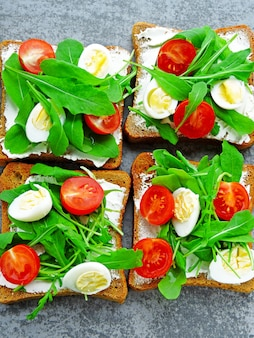 Fitness toasts with arugula, cream cheese, cherry tomatoes and quail eggs
