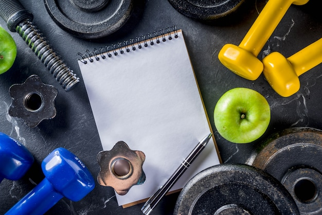 Fitness tools and dumbbells with blank notebook