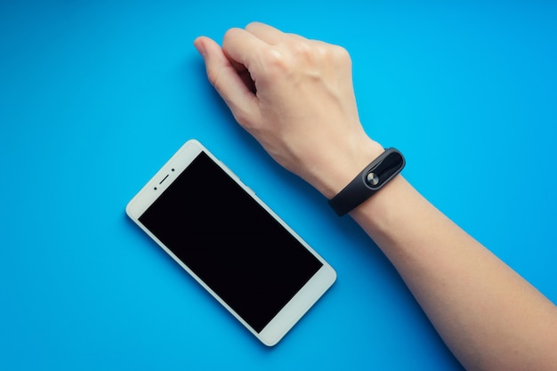 Fitness tracker on female hand on orange background and smartphone.