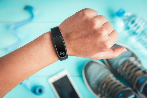 Fitness tracker on hand. sneakers, bottle of water, tape measure on blue, flat lay