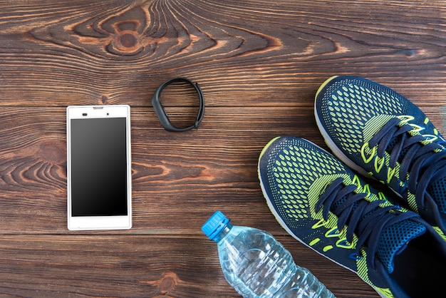 Fitness tracker, smart phone and sneakers on wooden table with copy space. healthy lifestyle background.