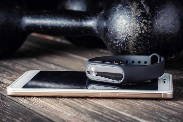 Fitness tracker, smartphone and iron dumbbells on a wooden background