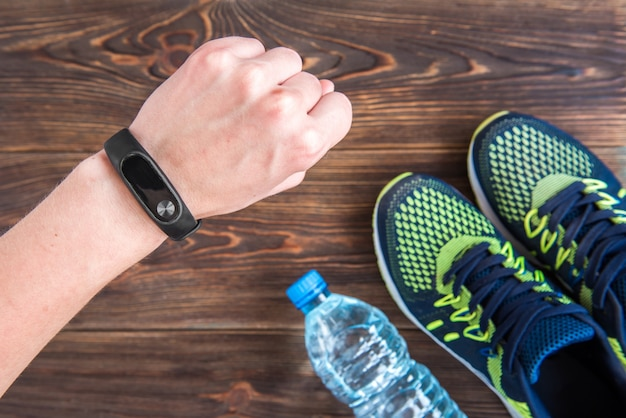 Fitness tracker and sneakers on wooden table with copy space. healthy lifestyle background.
